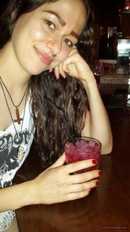 Mujer con un vaso en la mano y cejas tatuadas