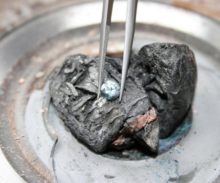 Pinzas sosteniendo un diamante sobre dos piezas de cenizas de difuntos