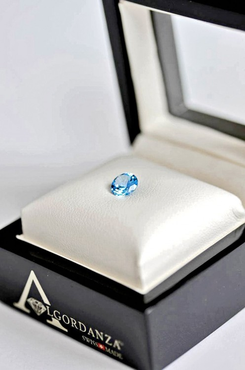Estuche de la empresa Algordanza con un pequeño diamante azul en su superficie en color blanco