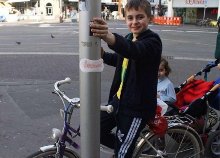 Chico en bicicleta junto a una columna con una toalla femenina feminista