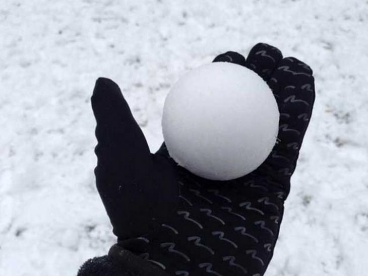 bola de nieve sostenida por una mano
