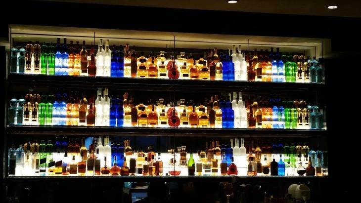 estante de bebidas alcohólicas acomodadas por colores