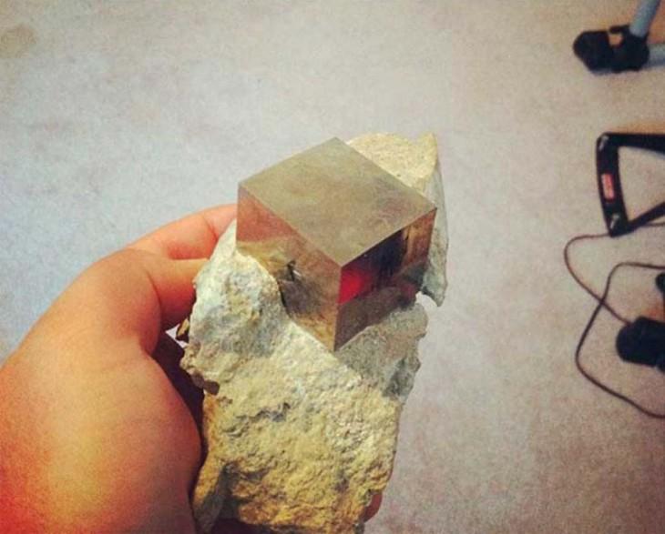 cubito de metal incrustado en piedra