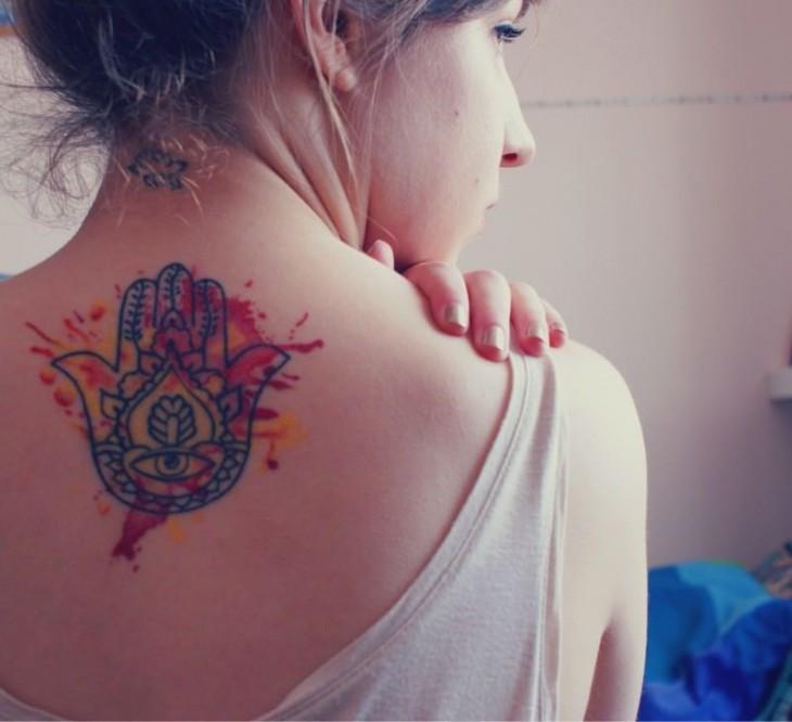 Chica con un tatuaje de la mano de fatima en la espalda
