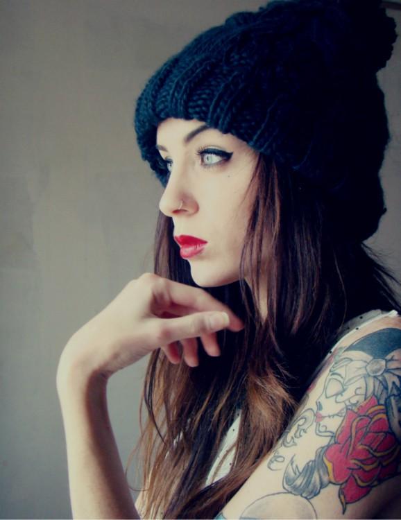 Chica con gorro negro y tatuajes en un brazo