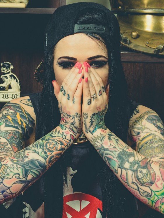 mujer con gorra negra y todos los brazos tatuados