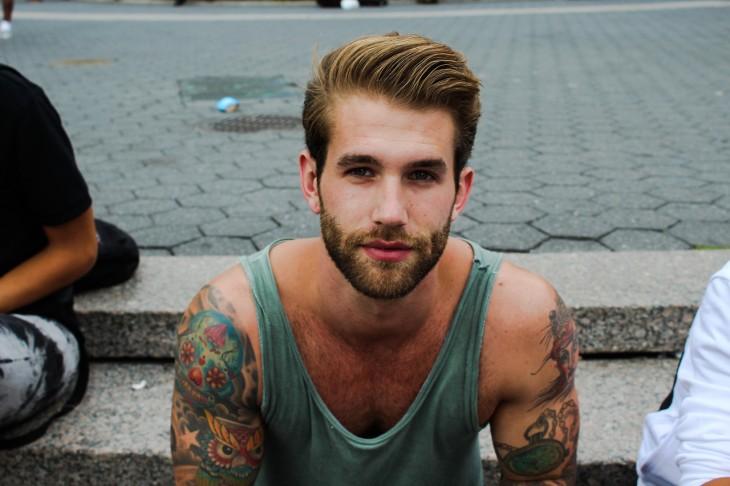 Hombre con barba y tatuajes en el cuerpo