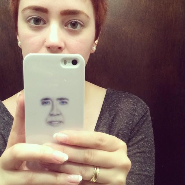 Foto de una chica con una funda de iphone con cara de nicolas Cage