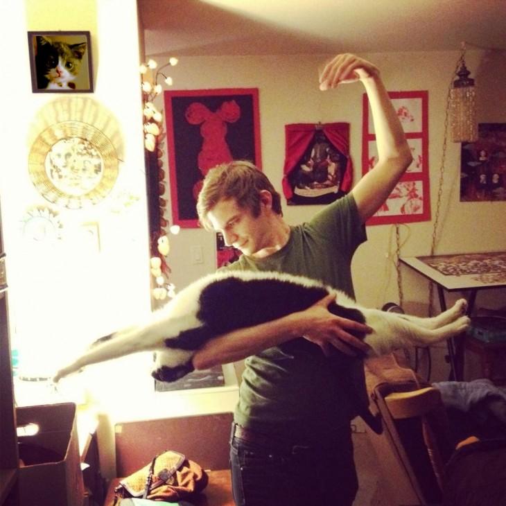Chico cargando con un brazo a un gato que esta en posición extendida (simulan bailar)