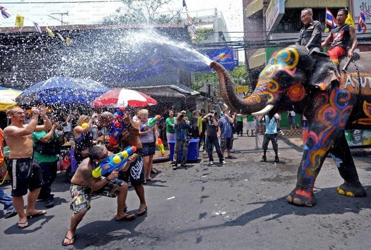elefante rociando con agua a personas en la calle