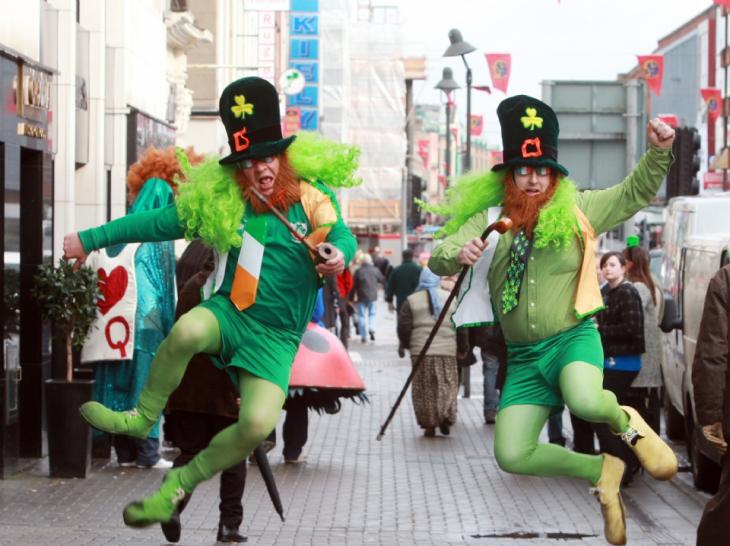 personas vestidas de duendes bailando y desfilando por la calle