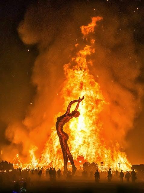 estatua de una mujer gigante quemándose en medio del desierto