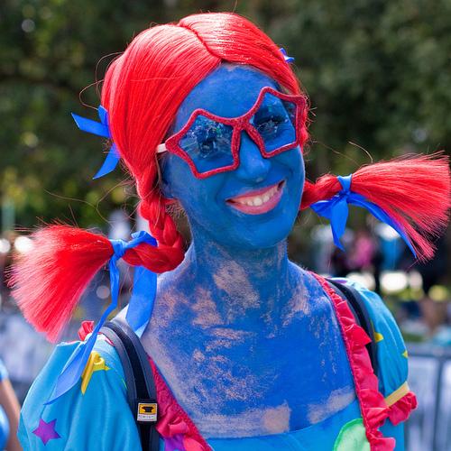 mujer con el cuerpo pintado de azul y peluca olor roja al igual que sus lentes