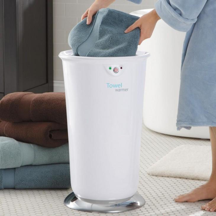 Mujer introduciendo una toalla en un recipiente que las calienta
