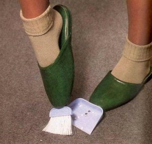 Zapatos con una escoba y un recogedor pequeños en la punta para cuando se tengan ocupadas las manos