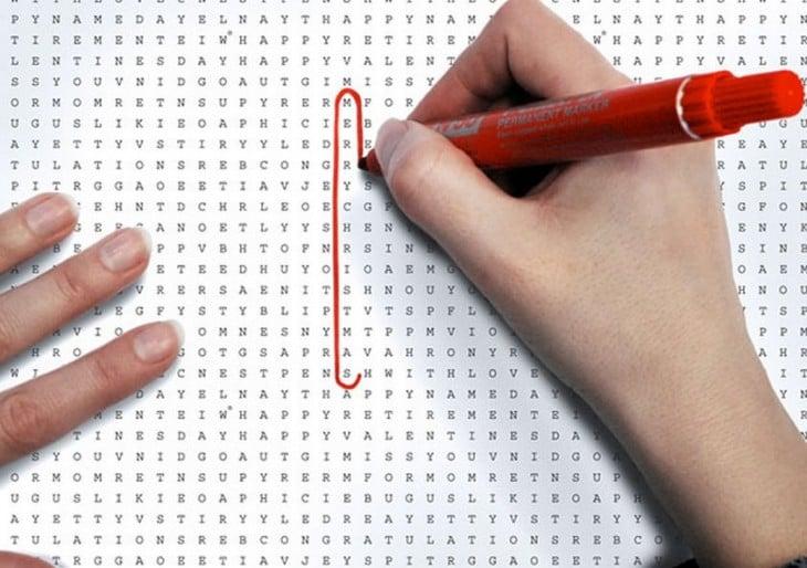 Una mano sobre el papel en forma de sopa de letras marcando una palabra con plumón rojo
