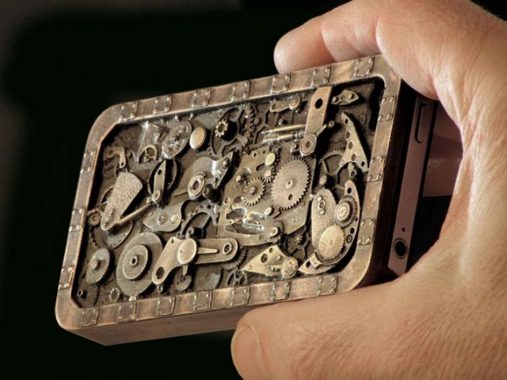 Mano de un hombre sosteniendo un Iphone con una funda de diseño de un mecanismo steampunk