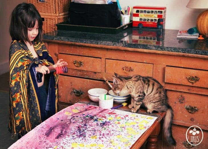iris grace haciendo una pintura en su mesa junto a su gato