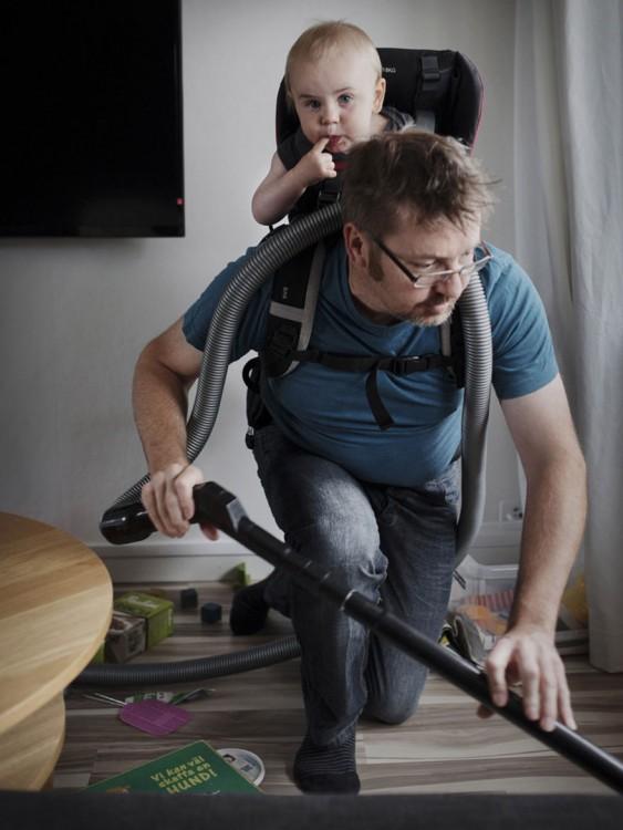 Papá limpiando mientras cuida a su hijo