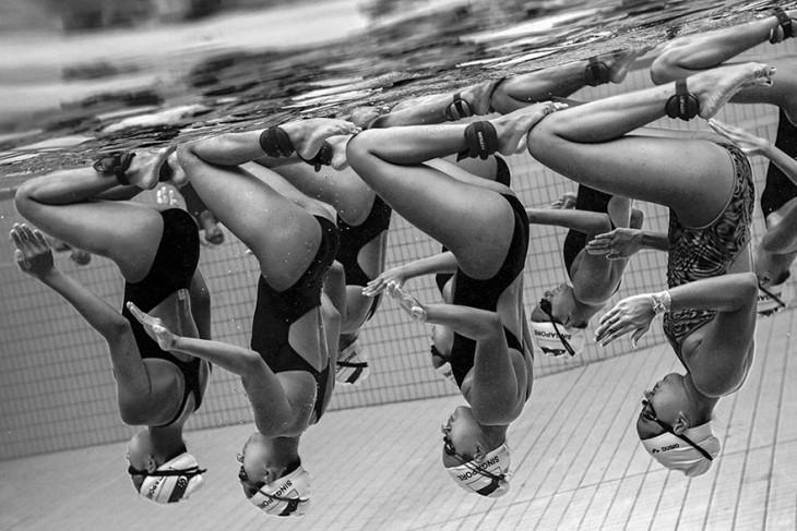 Mujeres de nado sincronizado de cabeza bajo el agua