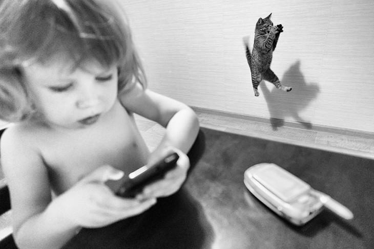 niña con un celular y de fondo un gato saltando