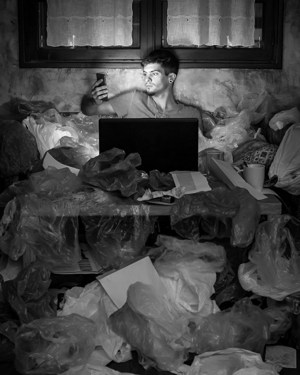Hombre con celular y computadora rodeado de basura