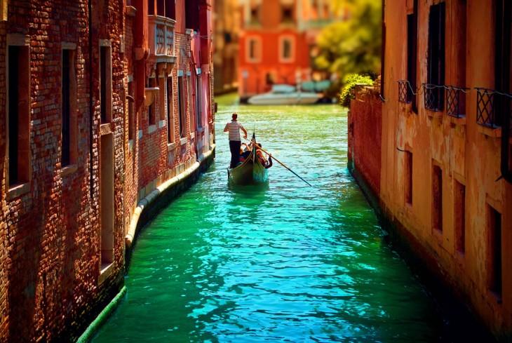 Pasillo en Venecia, Italia donde una persona pasea en canoa a los turistas