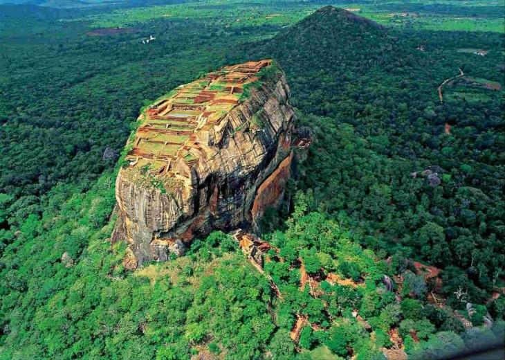 Imagen que muestra un paisaje con áreas verdes y una enorme montaña al centro