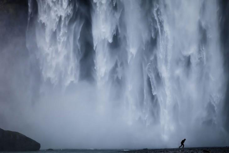 Persona corriendo debajo de unas enormes cascadas ubicadas en Islandia
