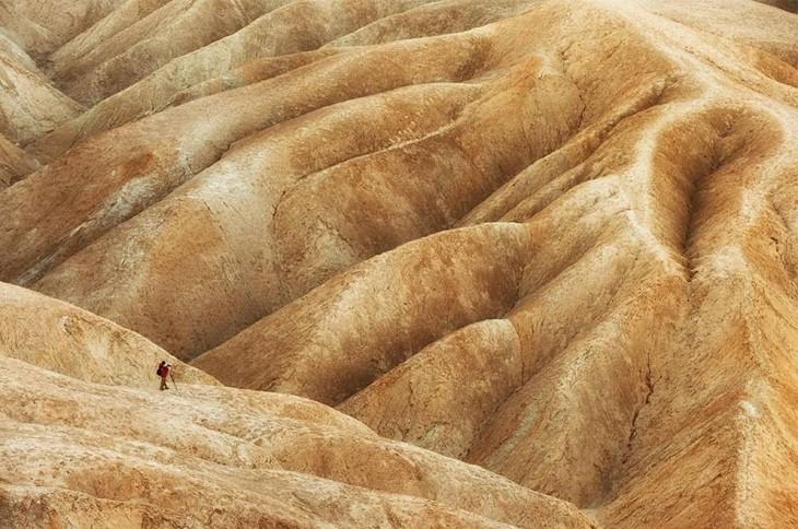 Hombre tomando una fotografía a unas montañas con algunas grietas y formas distintas