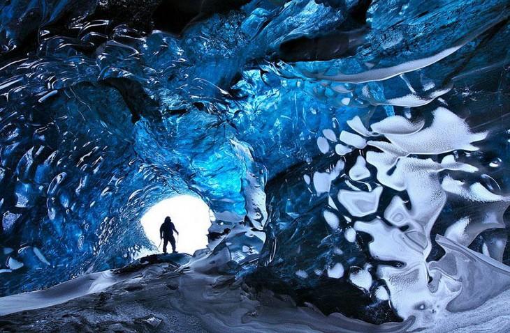 Un hombre parado en la entrada de un túnel denominado la cueva de cristal en Islandia