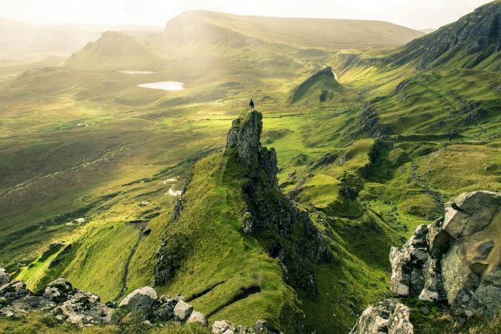 Hombre en la cumbre de una montaña con pastizales verdes en un ambiente cerca de Escocia