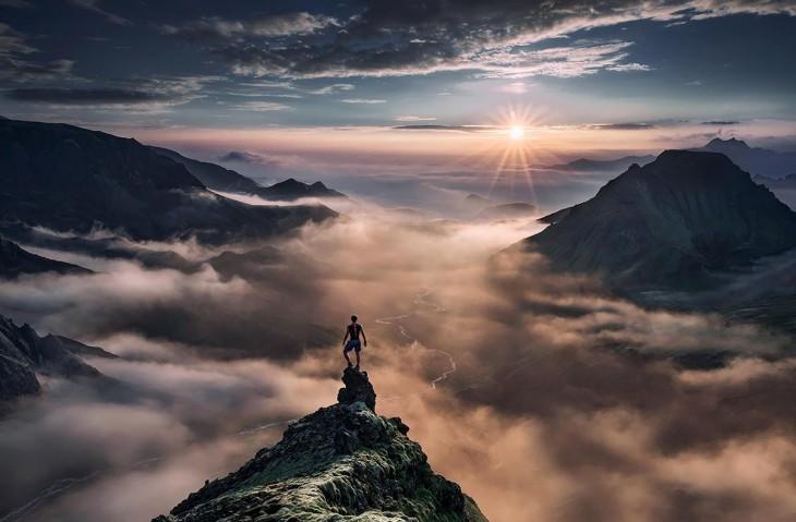 A medio atardecer un hombre parado en la cima de una montaña viendo en dirección a otras montañas
