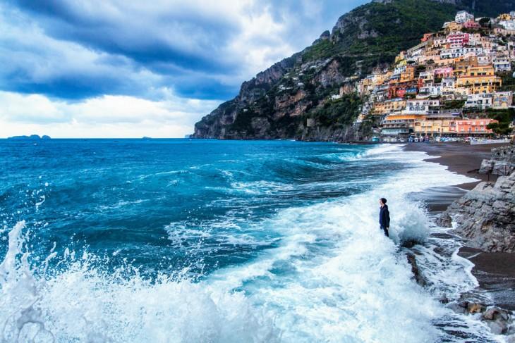 Un chico es golpeado por las olas a la orilla de una costa en Italia