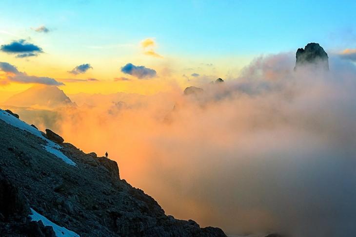 Persona a lo lejos a la orilla de una piedra de una montaña observando hacia otras montañas