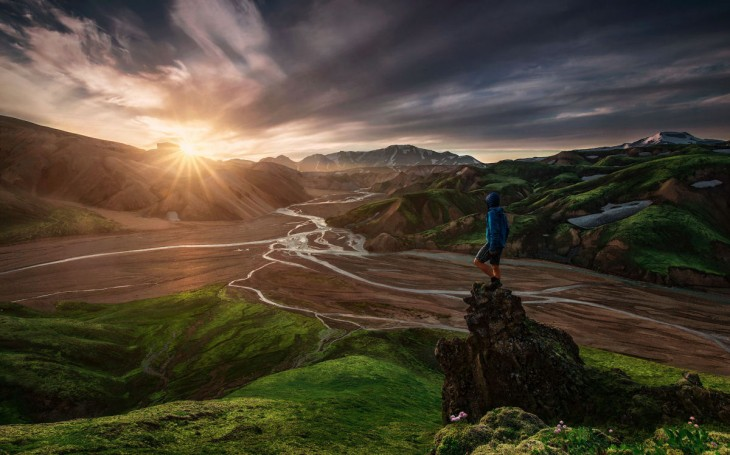 Hombre con vestimenta deportiva parado en una pequeña montaña viendo como sale el sol de otras montañas a su alrededor