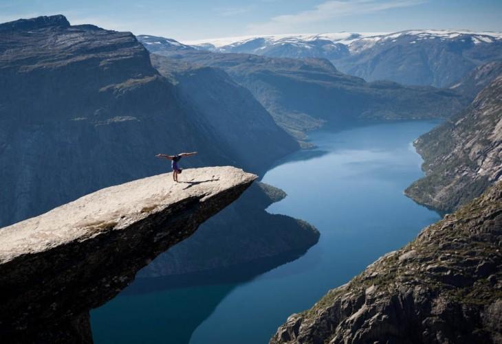 Chica practicando algunos paso de gimnasia a la orilla de una roca entre montañas en Noruega