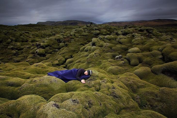 Hombre recostado sobre unas pequeñas montañas cubiertas en pasto verde