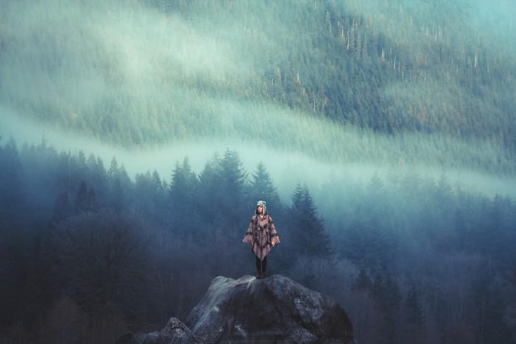 Chica parada sobre una piedra y al fondo un gran bosque repleto de pinos