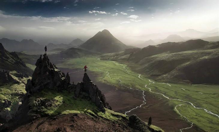 Dos personas paradas en la cumbre de unas montañas viendo hacia la parte baja