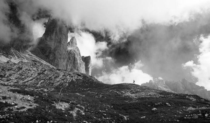 Una persona caminando hacia una montaña con el cidelo un poco nublado