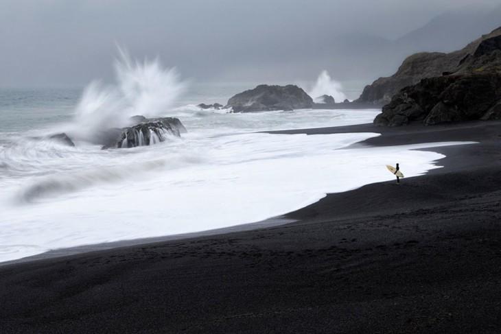 Hombre con una tabla de Surf parado a la orilla de un mar donde las olas chocan con las rocas