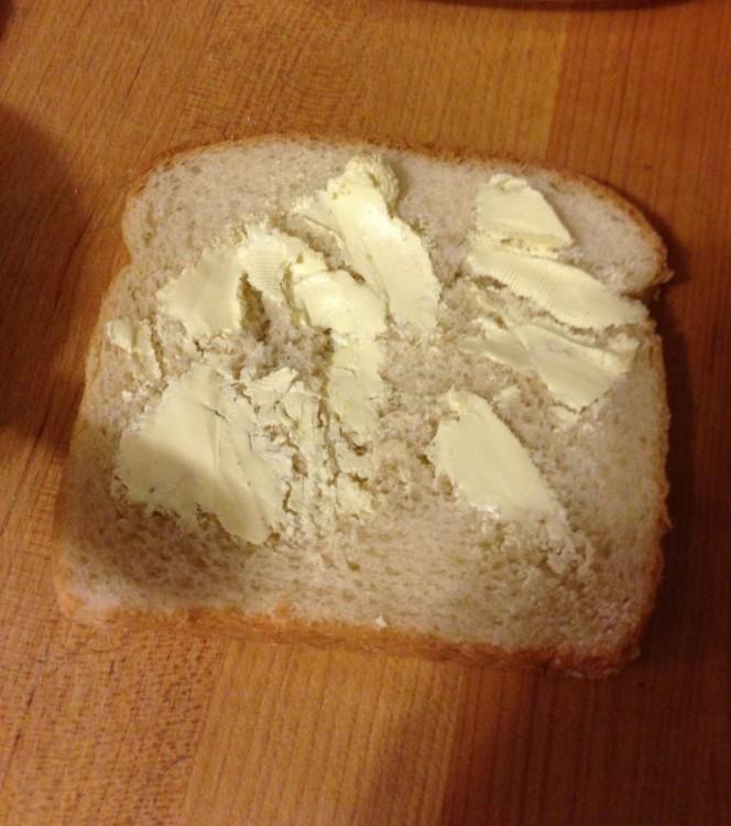 trozo de pan destrozado con mantequilla