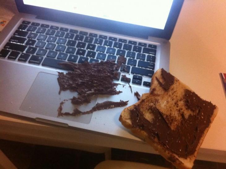 Laptop llena de nutella con un pedazo de pan