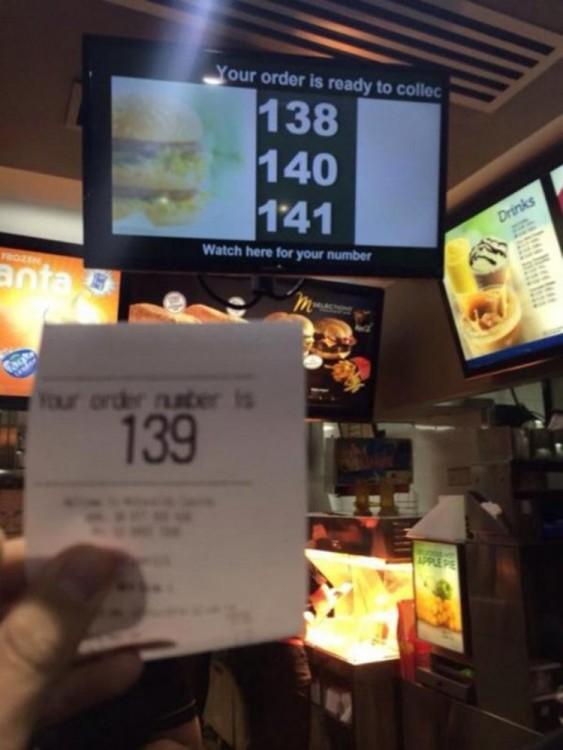 Mano mostrando el número de turno en un local de comida rápida