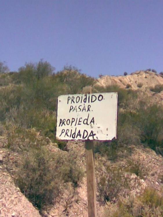 Letrero sostenido con un palo en un lugar fuera de la ciudad que prohíbe el paso