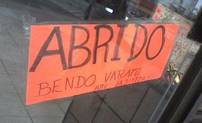 Letrero en color naranja con muchas faltas de ortografía en la puerta de un negocio