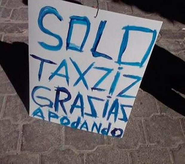 Letrero blanco con tinta azul donde dice algo acerca de los taxis
