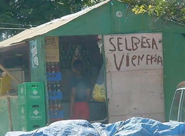 Una persona dentro de una tienda donde fuera hay un letrero con falta de ortografía que dice que se venden cervezas frías