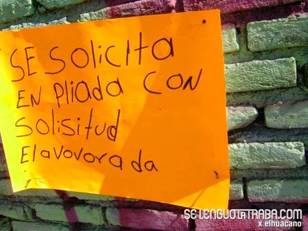 Cartulina en color naranja con un letrero con pésima ortografía sobre un pared